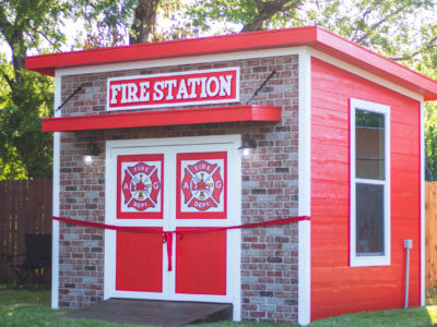 fire station themed playhouse brick look facade with red and white siding and fire station emblems